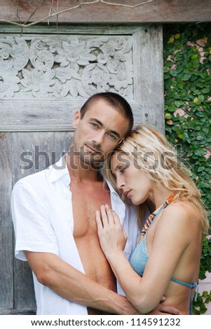 Attractive young couple hugging while on vacation in a tropical destination. - stock photo