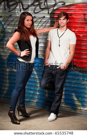 Attractive young couple in an urban fashion lifestyles setting with a graffiti background. - stock photo