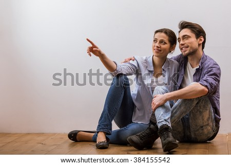 Attractive young couple in casual clothes talking, pointing and looking away while sitting on wooden floor against white background - stock photo