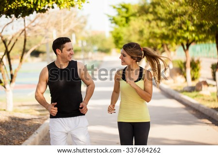 Attractive young couple in sporty outfits running together and having some fun at a park - stock photo