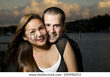 Attractive young couple in twilight embrace on river with dramatic sky. Male is caucasian, female is Filipino. - stock photo