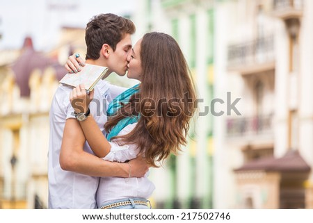 Attractive young couple kissing in a classic architecture city during their vacation. Young couple in love, hugging on the street.Happy young couple kissing on the city street. - stock photo