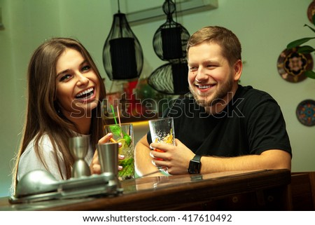 Attractive young couple laughing at the bar with alcoholic cocktails - stock photo