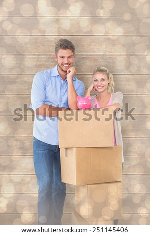 Attractive young couple leaning on boxes with piggy bank against light glowing dots design pattern - stock photo