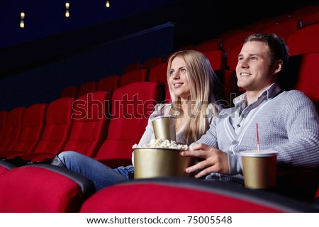 Attractive young couple looking at a movie theater - stock photo