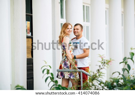 Attractive young couple lovely hugging in the city and looking at the camera. Photo with copy space at the left - stock photo