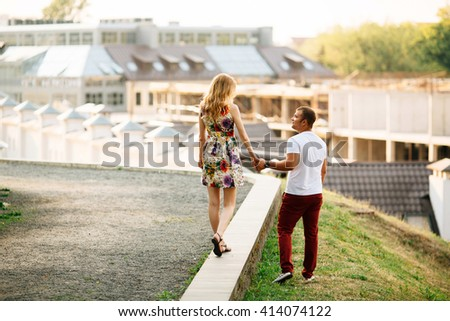 Attractive young couple lovely walking in the city and looking each other. Photo with copyspace at sunny day - stock photo