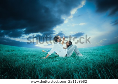 Attractive young couple lying down against blue sky over green field - stock photo