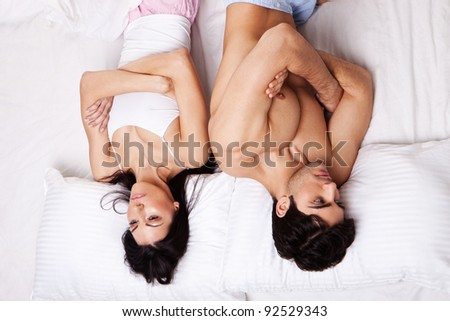Attractive young couple lying in bed with folded arms and turned away from each other following an argument. - stock photo