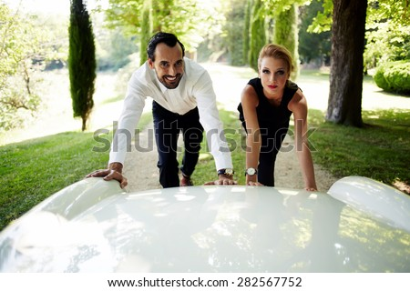Attractive young couple of travelers faced with the problem, their luxurious new white car broken during amazing summer trip,beautiful Caucasian couple trying to push the car to continue their journey - stock photo