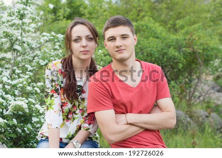 Attractive young couple on a spring date posing close together in front of a tree covered in white spring blossom while enjoying a day in the country - stock photo