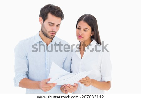 Attractive young couple reading their bills on white background - stock photo