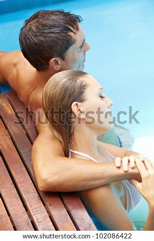 Attractive young couple relaxing together in swimming pool with blue water - stock photo
