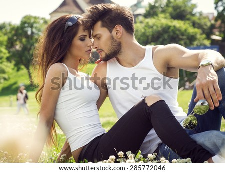 Attractive young couple resting on the grass and touching each other - stock photo