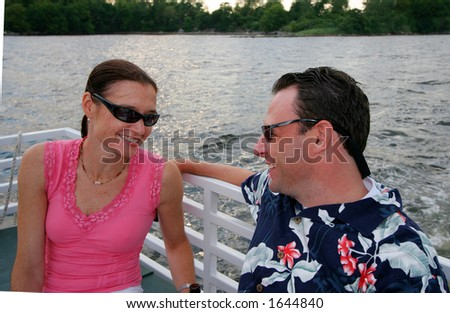 attractive young couple riding on boat - stock photo