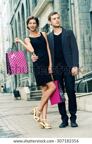 Attractive young couple shopping in the city. Seasonal sale. Fashion shot. - stock photo