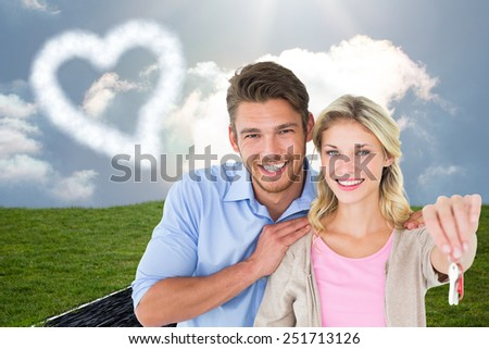 Attractive young couple showing new house key against road on grass