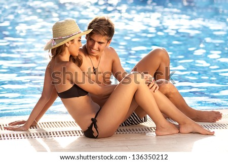 Attractive young couple sitting close together in their swimsuits at the edge of a sparkling blue swimming pool having a romantic chat