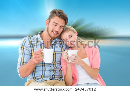 Attractive young couple sitting holding mugs against tropical island in blue ocean - stock photo