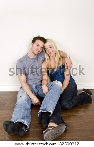 Attractive young couple sitting in their new home - stock photo