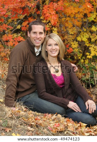 attractive young couple sitting together outdoors in fall colors - stock photo