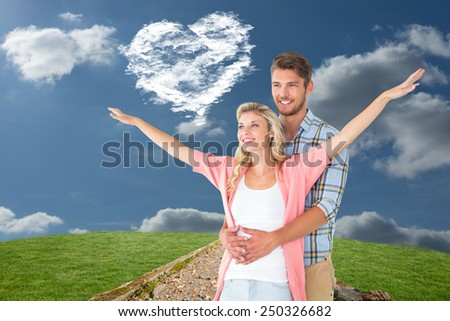 Attractive young couple smiling and embracing against cloud heart - stock photo