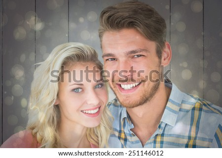 Attractive young couple smiling at camera against black abstract light spot design - stock photo