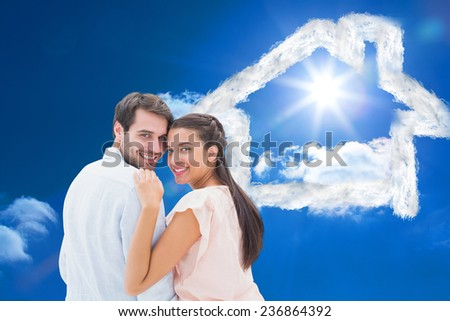 Attractive young couple smiling at camera against bright blue sky with clouds - stock photo