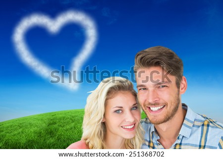 Attractive young couple smiling at camera against green hill under blue sky - stock photo
