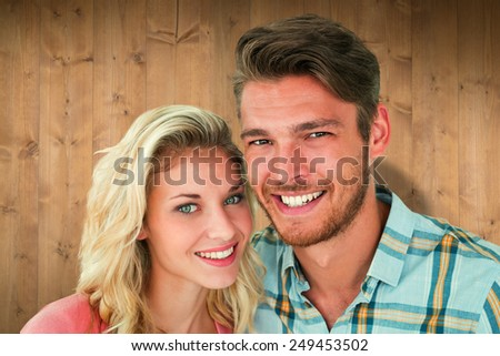 Attractive young couple smiling at camera against wooden planks
