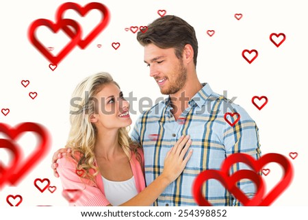 Attractive young couple smiling at each other against hearts - stock photo