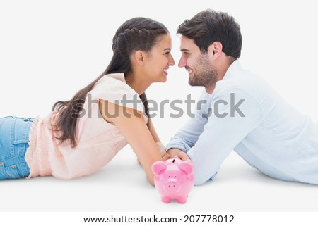 Attractive young couple smiling at each other on white background - stock photo