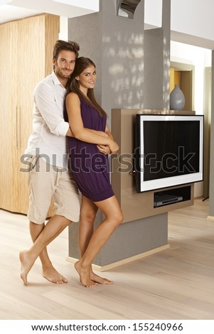 Attractive young couple standing in living room of stylish home, smiling happy. - stock photo
