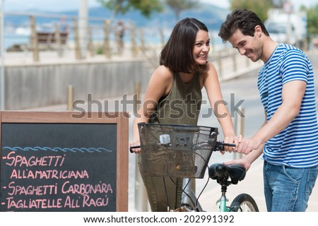 Attractive young couple standing outside a tropical restaurant chatting while holding a bicycle with a carrier basket as they enjoy a summer vacation in the tropics - stock photo
