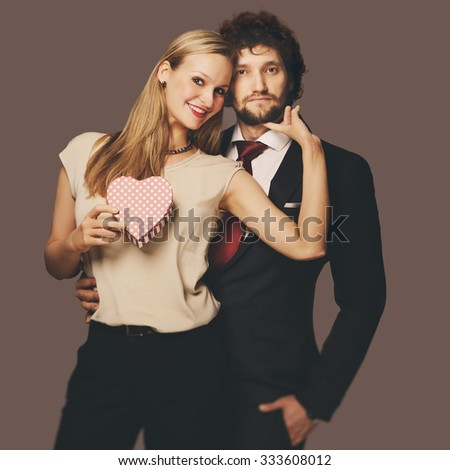 Attractive young couple with paper heart - stock photo