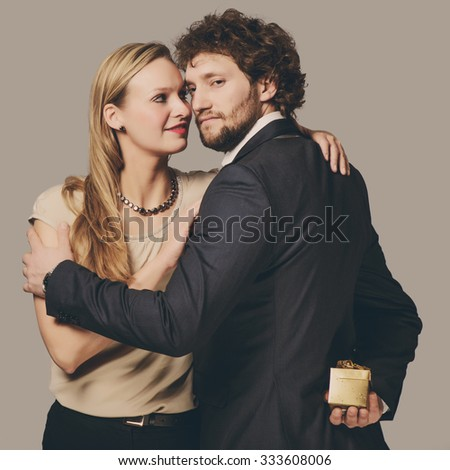 Attractive young couple with present box - stock photo
