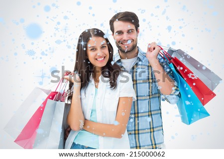 Attractive young couple with shopping bags against snow falling - stock photo