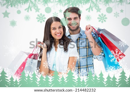 Attractive young couple with shopping bags against snowflakes and fir trees in green - stock photo