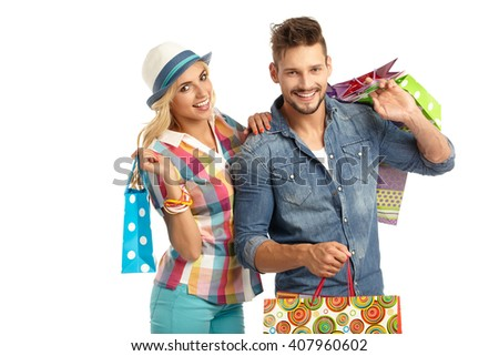 Attractive young couple with shopping bags on white background
