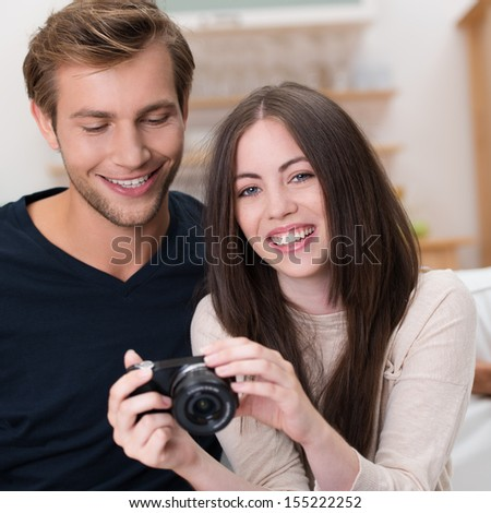 Attractive young couple with warm friendly smiles looking at their photographs on the back of the camera as they sit together in the living room