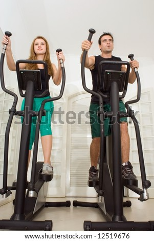 Attractive young couple working out on elliptical trainers at the gym. Facing the same direction - stock photo