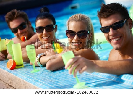 Attractive young couples refreshing in swimming pool, drinking cocktail, smiling.