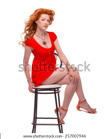 Attractive young curly redhead woman in red dress sitting on the chair - stock photo