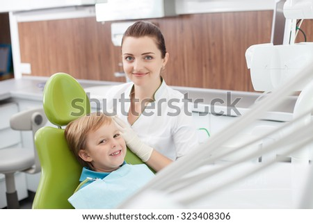 Attractive young dental doctor is treating teeth of kid. The boy is sitting in medical chair with joy. The woman and boy are smiling. They are looking at camera happily - stock photo