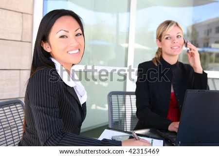Attractive, young, diverse business woman team at office working - stock photo