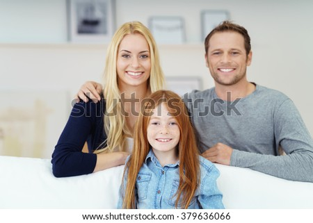 Attractive young family relaxing at home posing together in the living room with the little girl seated on a sofa and her parents behind