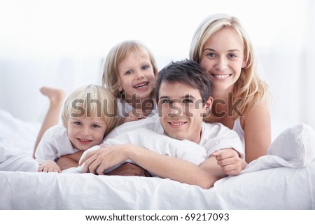 Attractive young family with children in the bedroom - stock photo