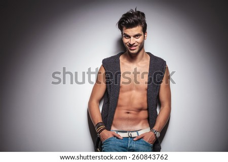 Attractive young fashion man leaning on a wall with both hands in his pocket, looking at the camera. - stock photo