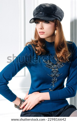 Attractive young fashion model in hat near door sitting cube - stock photo