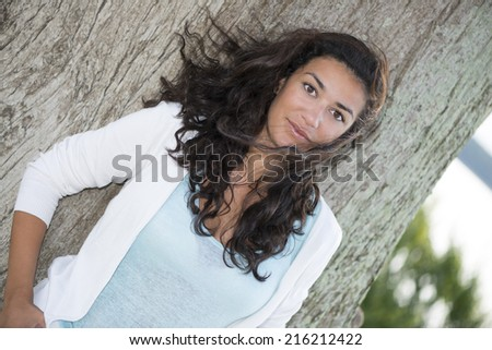 Attractive young fashion model looking at camera in nature on large trunk tree. The wind playing with her long brown hair. Beauty in nature